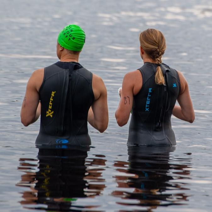 Back view of two people standing in water